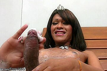 Dark haired shemale puts tons of lotion on her big cock