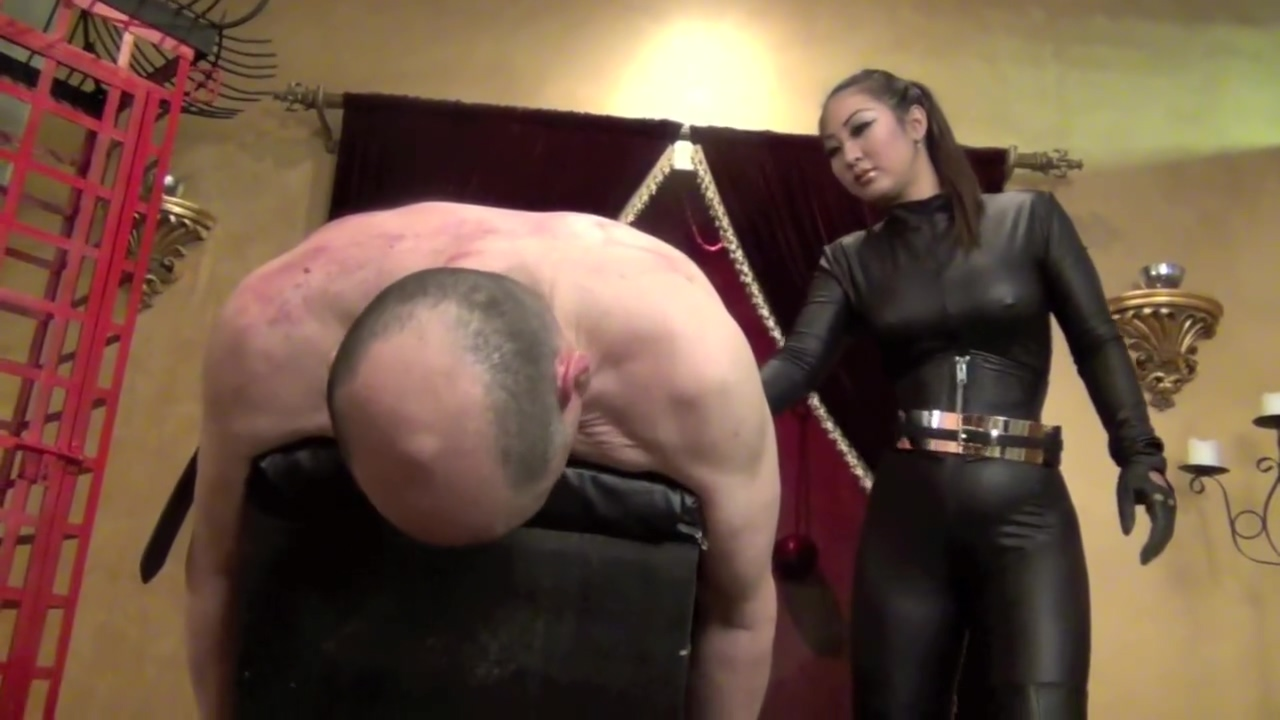 Asian mistress in leather catsuit slaps and paddles her slave
